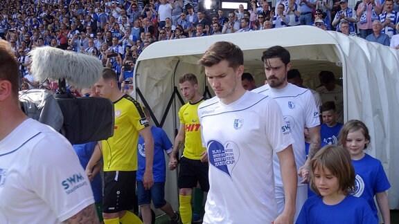 Spieler laufen ins Stadion ein.