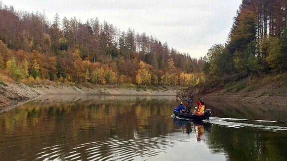 Drei Männer fahren mit einem kleinen Boot über einen Stausee