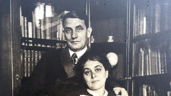Ein historisches Foto zeigt ein Ehepaar, das auf einem Sessel vor einem Bücherregal posiert