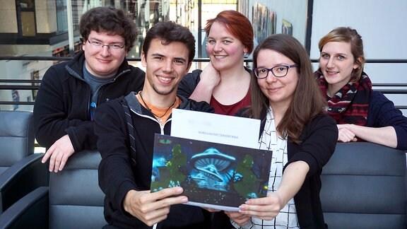 Zwei Männer und drei Frauen an einer Couch halten ein Bild in die Kamera und lächeln