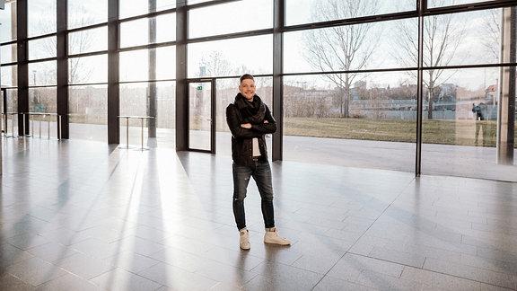 Ein Mann (Robin Pietsch) steht vor einer Glasfassade, im Hintergrund strömt Licht ein