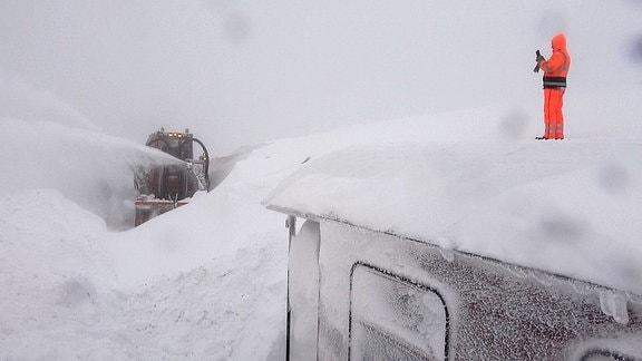 Eine Schneefräse fährt auf dem Brocken durch hohe Berge von Schnee.