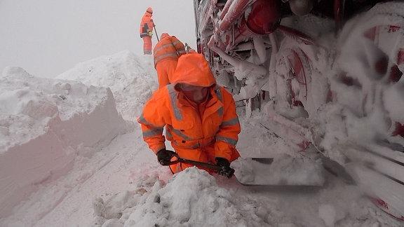 Mitarbeiter in orangenen Warnwesten schaufeln Schnee an den Rädern einer Lok.