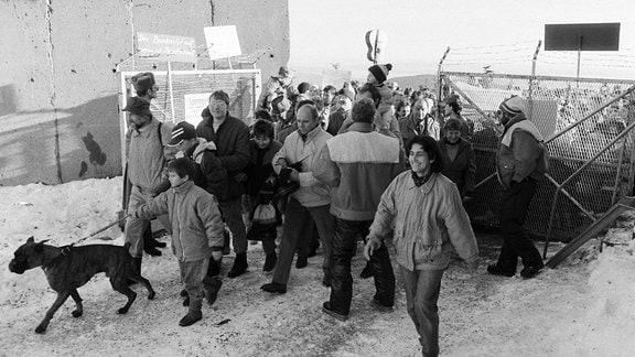 """Menschen laufen am 03.12.1989 nach einer von der DDR-Bürgerbewegung organisierten """"Wanderung"""" zum Brocken duerch das eben geöffnete Tor zu den militärischen Einrichtungen auf dem Brocken (Sperrgebiet mit Abhöranlagen der Stasi und der Sowjet-Truppen)."""