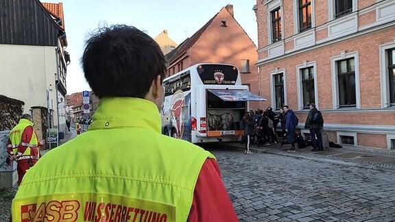 Ein Rettungssanitäter steht vor einem Schulbus mit Kindern.