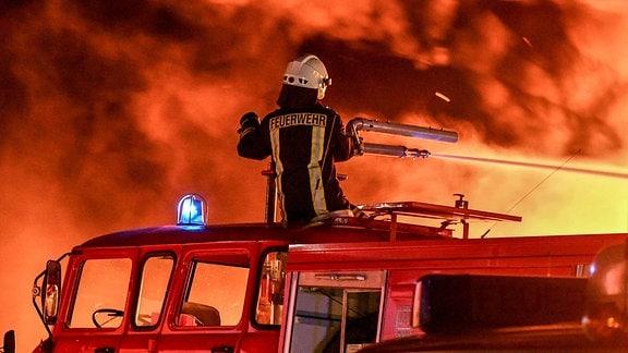 Ein Feuerwehrmann löscht vom Feuerwehrfahrzeug aus einen Brand.