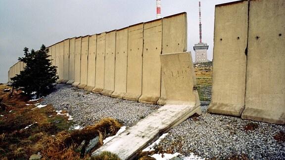 Durch ein umgekipptes Mauerelement kann man auf das Brockenplateau schauen