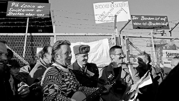gut gelaunte Menschen vor dem Grenzzaun des Brockens