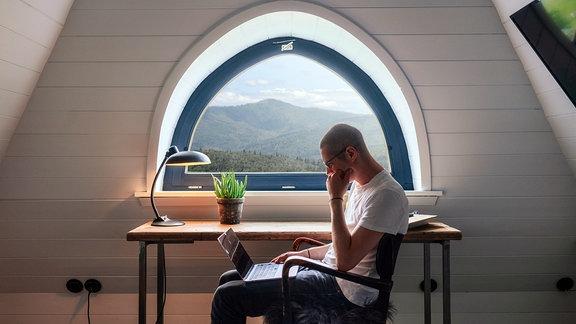 Ein Mann sitzt mit einem Laptop auf dem Schoss in einem Zimmer mit Aussicht über einen Wald