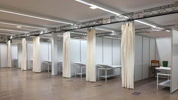 Mehrere Arztpritschen stehen getrennt durch Wände im Corona-Impfzentrum in Quedlinburg.