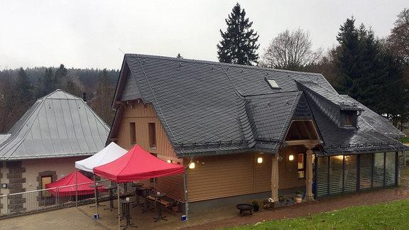 Modernes Haus mit Holzfassade und Pavillions davor.