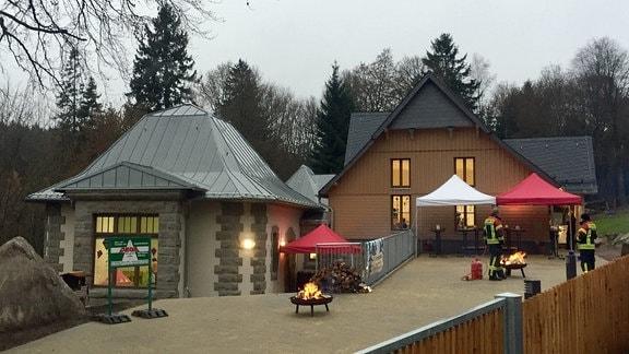 Zwei Häuser im Wald mit Pavillions, Feuerschalen und Feuerwehrleuten davor.