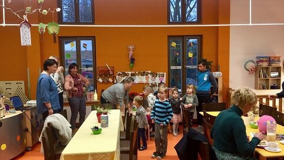 Gruppenraum mit Kindern und Erziehern in Kita.