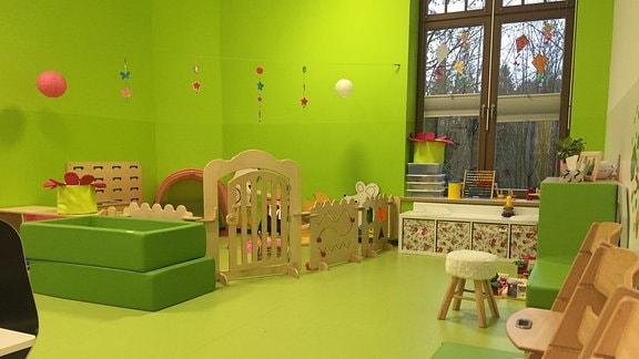 In grün gehaltener Raum mit Spielzeug in Kita.