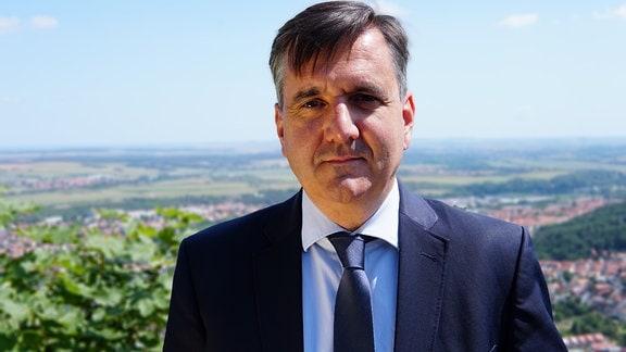 Thomas Balcerowski in einer Nahaufnahme auf einer Höhe stehend mit einem Tal hinter sich.