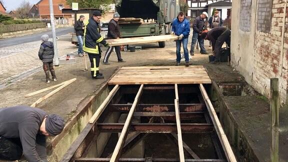 Männer legen Bretter auf einen Schacht.