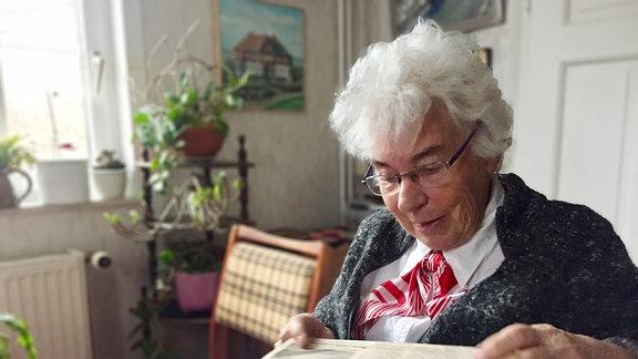 Alte Frau mit weißen Haaren und rotem Halstuch liest alte Zeitung