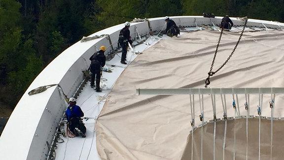 Bauarbeiter breiten Stoff auf dem Dach der Schierker Eisarena aus