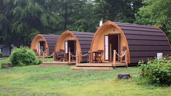 Moderne, runde Holzhütten auf einem Campingplatz.
