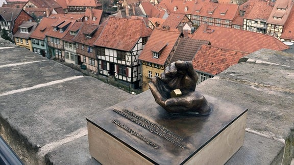 Eine Skultur aus Händen, die schützend ein Haus halten. Im Hintergrund die Quedlinburgs Fachwerkhäuser.