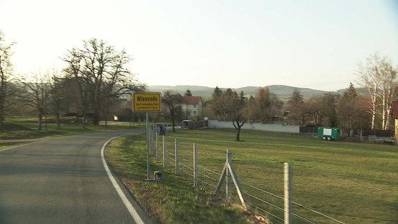 Landstraße mit Ortseingangsschild von Wienrode.