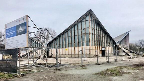 Gebäude mit spitz zulaufendem Dach mit Baustelleninformationsschild