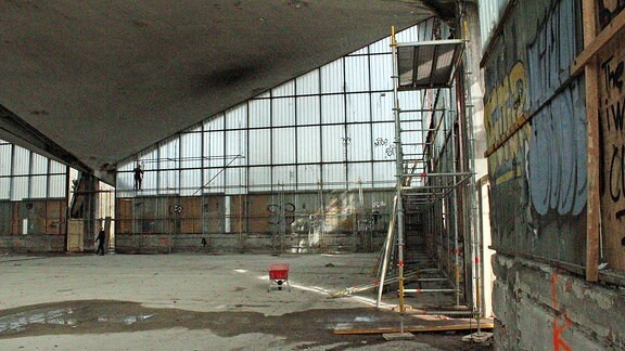 Leerstehende Halle mit Betonfußboden, Glasfront und Gerüst an einer Wand