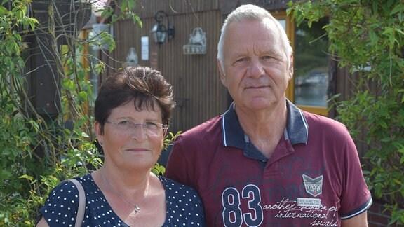 Ein ältere Frau und ein älterer Herr stehen vor einem Holzhaus