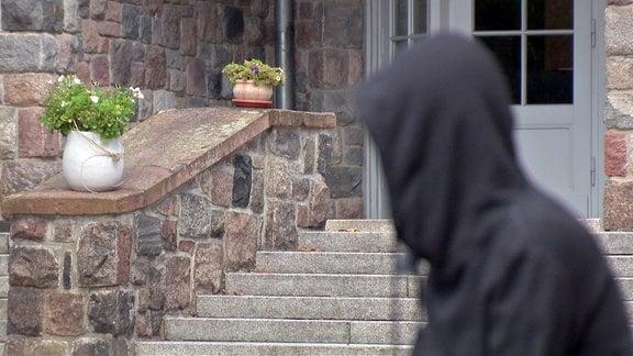Ein junger Mann steht vor einem Treppenaufgang