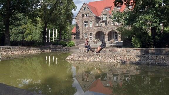 Zwei Menschen sitzen vor der Kulisse einer altehrwürdigen Villa