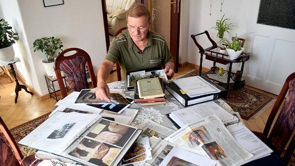 Ein Mann hat Postkarten, Fotos und Artikel über den Klusfelsen gesammelt.