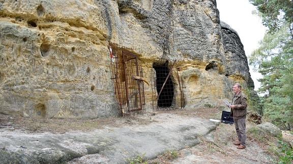 Ein Mann steht vor einem verschlossenen Eingang.