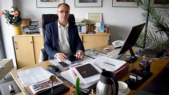 Der Oberbürgermeister von Halberstadt, Andreas Henke, sitzt an einem Schreibtisch.