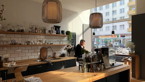 Ein Mann sitzt in einem Cafe am Fenster