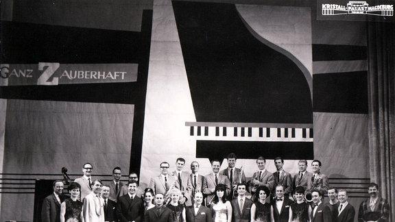 Alte Schwarzweißaufnahme von Menschen auf der Bühne des Magdeburger Kristallpalastes