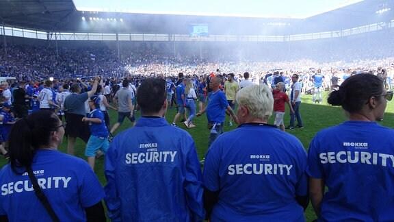 Im Vordergrund Security, im Hintergrund strömen Fans auf das Spielfeld.