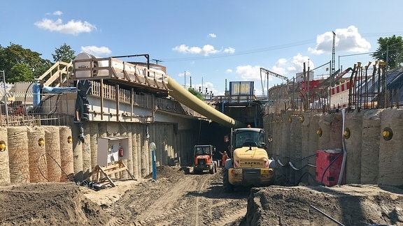 Blick in eine unbefestigte Tunneleinfahrt, in der zwei Bagger arbeiten