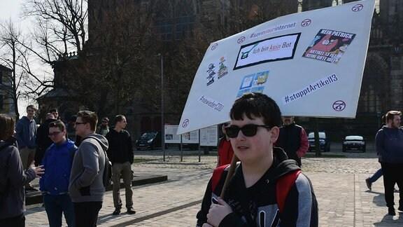 Junger Mann hält ein Schild gegen Artikel 13 hoch.