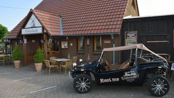 Ein Mietwagen steht vor einer Ferienanlage