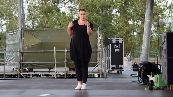 Eine junge Frau steht neben der Bühne und übersetzt etwas in Gebärdensprache.