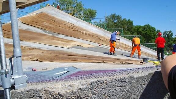 Blick auf die stark gebogene  Dachschale der Hyparschale, auf der Bauarbeiter Karbonfasern eingießen.