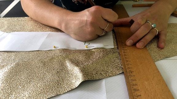 Schnittmuster werden an einem Stoff angelegt und gemessen