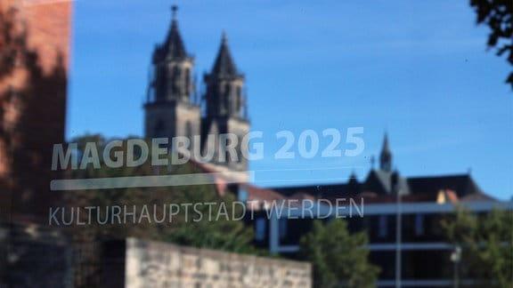 Der Magdeburger Dom spiegelt sich in einer Scheibe auf der Magdeburg 2025 steht.