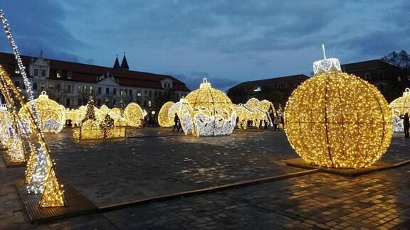 Das nasse Kopfsteinpflaster des Magdeburger Domplatzes wird von zahlreichen aus Lichterketten gebauten Figuren wie Weihnachtskugel und Pferden beleuchtet.