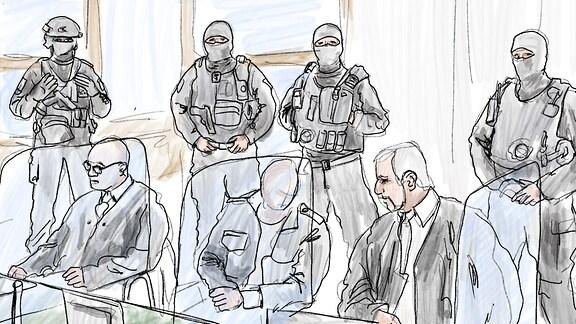 Der Angeklagte zwischen seinen Anwälten, dahinter stehen Sicherheitskräfte