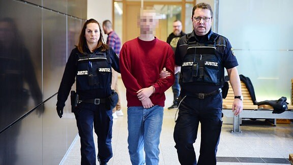 Ein Mann wird von 2 Polizisten untergehakt.