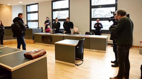 Verschiedene Personen in einem Gerichtssal.