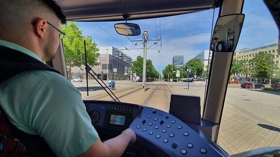Blick über die Schulter eines Straßenbahnfahrers aus dem Cockpit.