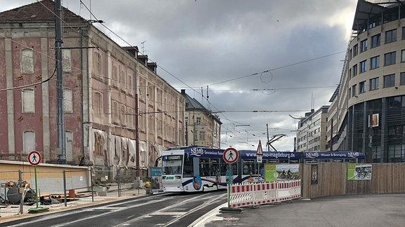 Straßenbahn fährt durch Baustelle vor Tunnel.