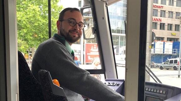 Ein Mann sitz am Steuer einer Straßenbahn und schaut lächelnd in die Kamera.